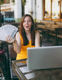 woman-outdoors-street-coffee-shop-cafe-sitting-with-modern-laptop-pc-computer-holds-hand-bunch-dollars-banknotes
